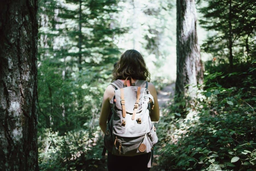 minimalist living - woman in sleeveless top and backpack surrounded by trees during daytime