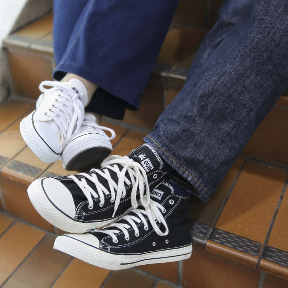 Two people wearing sneakers sitting down on stairs, only showing legs and feet.