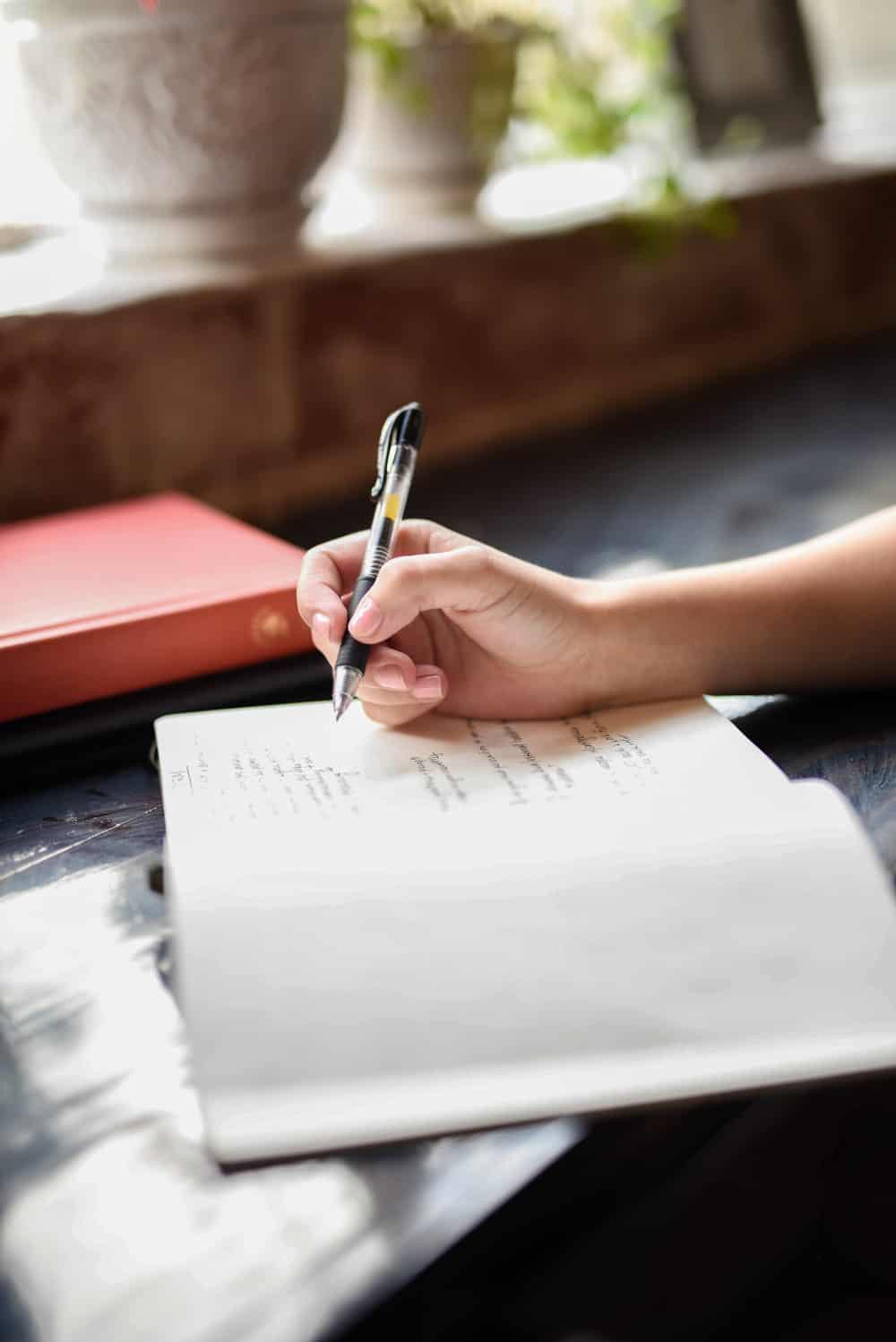 Journaling in cafe. Close up of hand holding a pen writing in notebook.