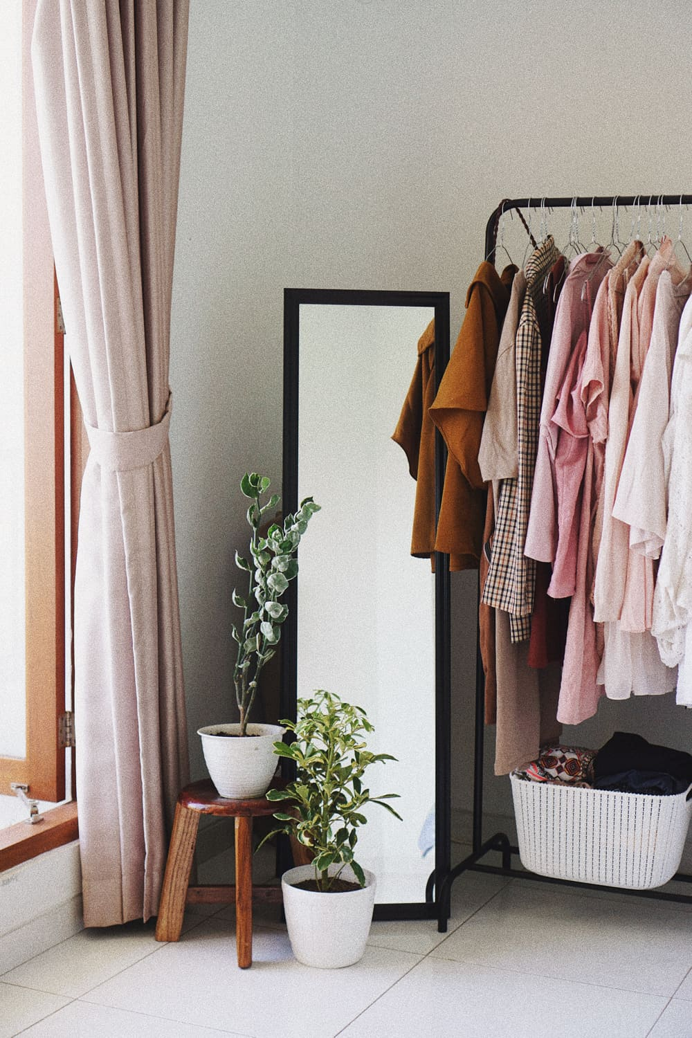 Corner of room with window, mirror, plants and clothes hanger with clothes.
