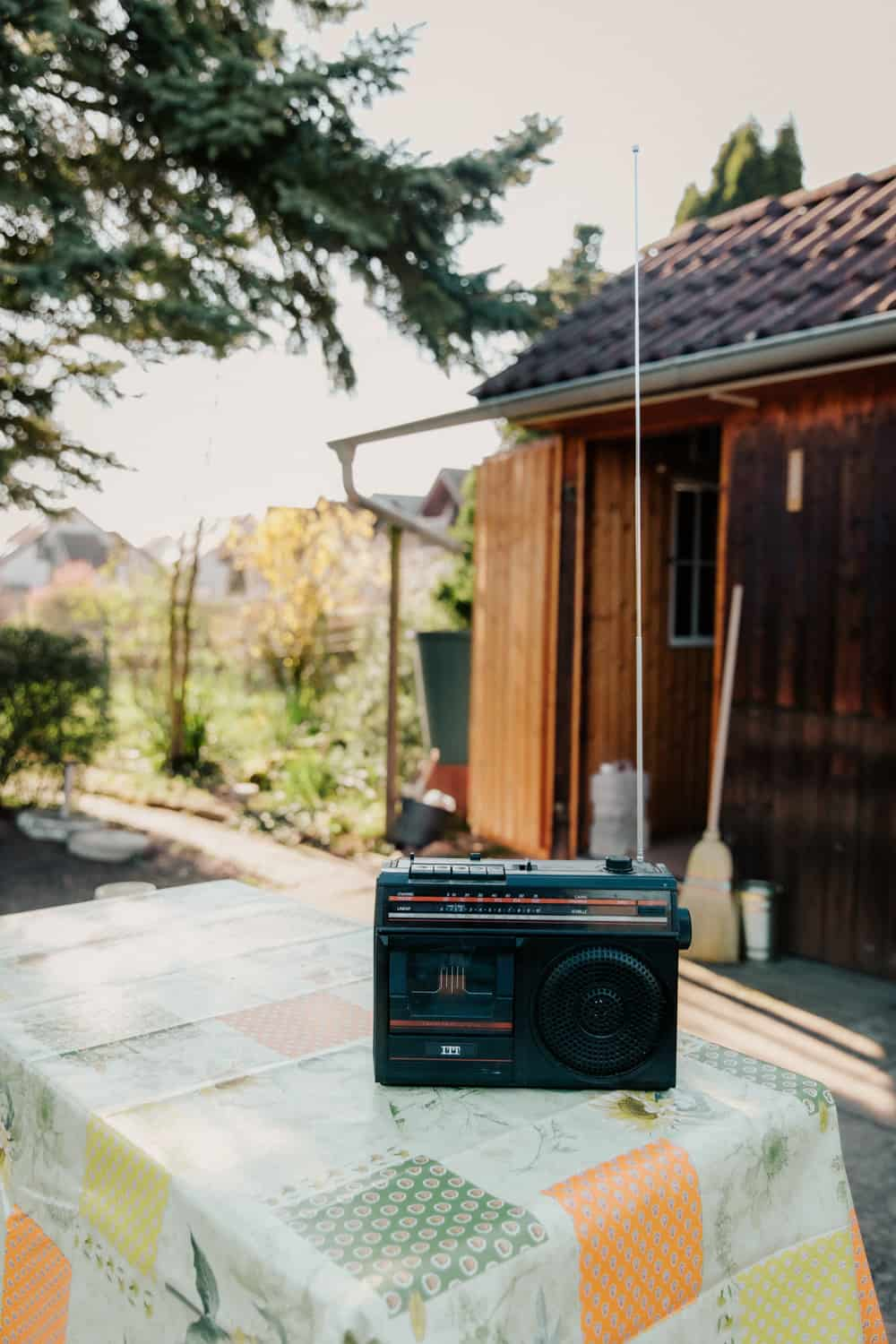 Old cassette and radio player on table outside.