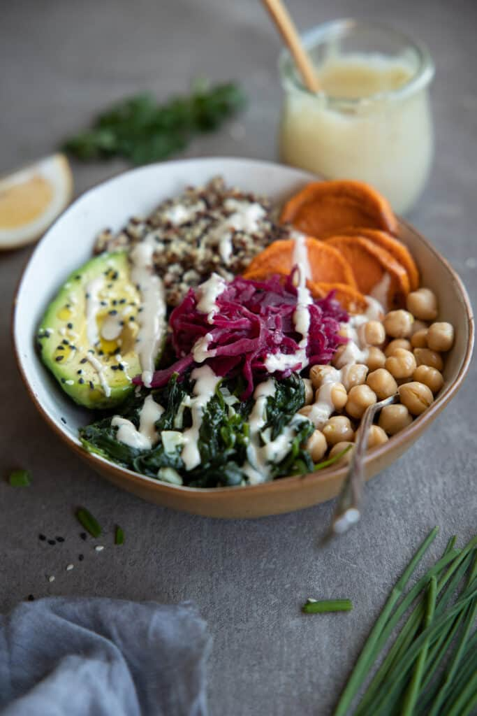 Quinoa Buddha bowl with tahini dressing drizzled over the top.