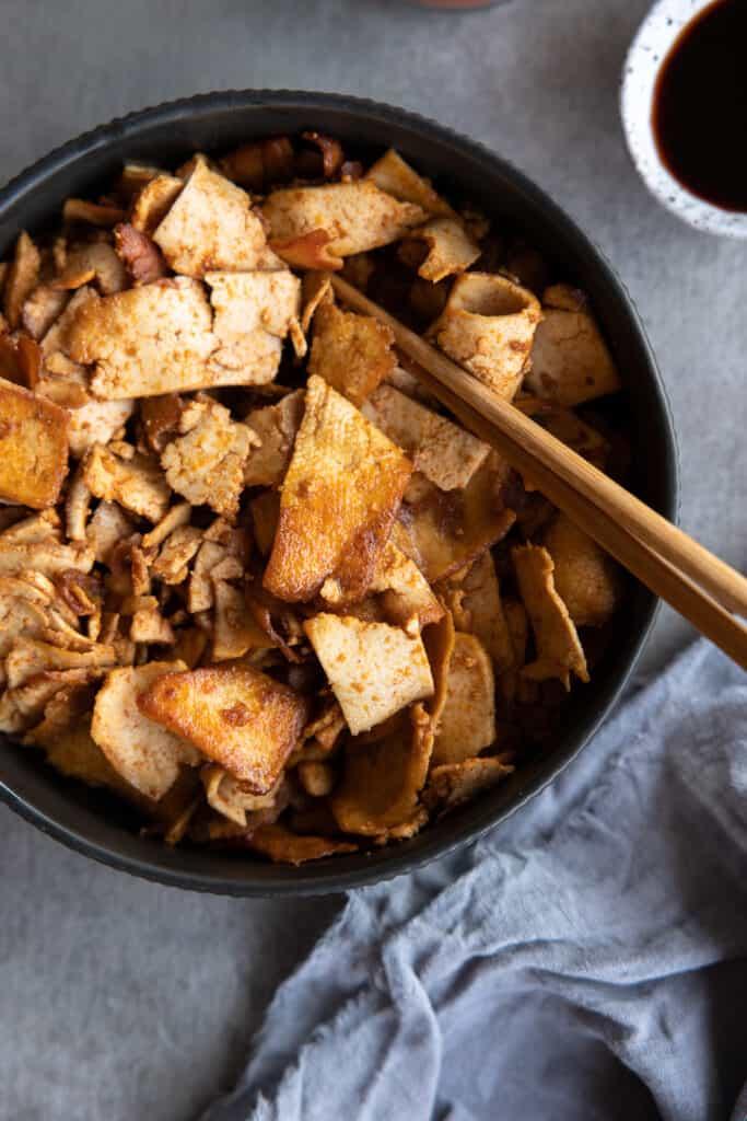 Crispy tofu in a bowl with chopsticks.