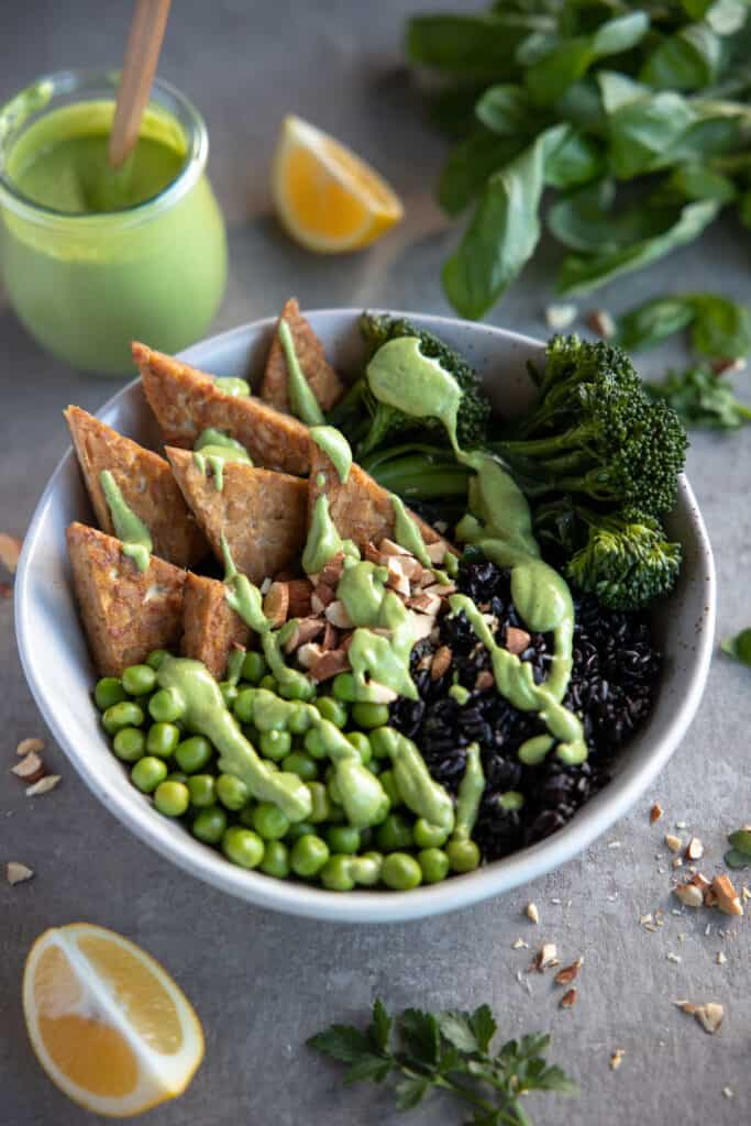 Buddha bowl with green goddess dressing spread over the top.