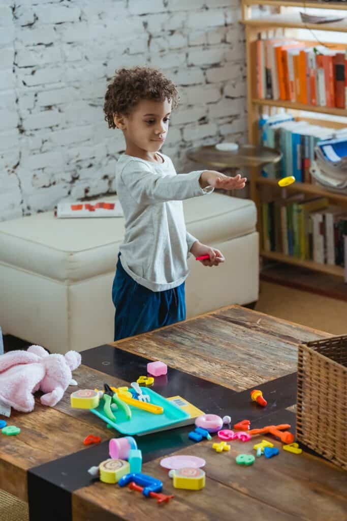 Child playing with toys on the coffee table in lounge room.