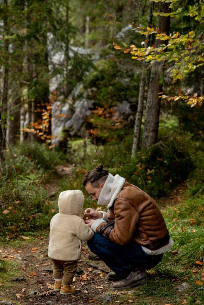 Father and toddle in a forest looking at something in the father's hands.
